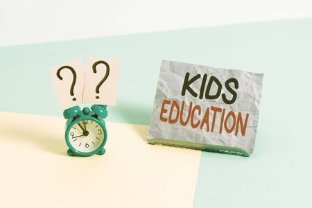 Handwriting text Kids Education. Conceptual photo action or process of educating kids or of being educated Mini size alarm clock beside a Paper sheet placed tilted on pastel backdrop Banque d'images - 140069404