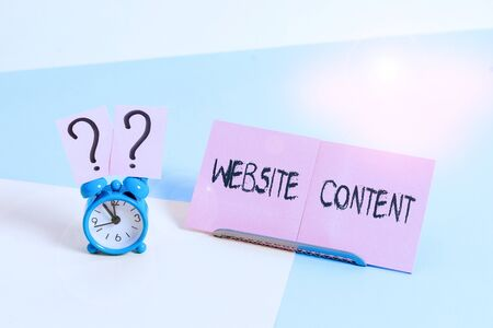 Word writing text Website Content. Business photo showcasing single most important and sought after commodity on the web Mini size alarm clock beside a Paper sheet placed tilted on pastel backdrop