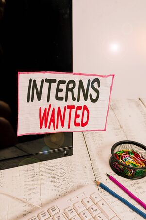 Handwriting text writing Interns Wanted. Conceptual photo temporary position with an emphasis on the job training Note paper taped to black computer screen near keyboard and stationary