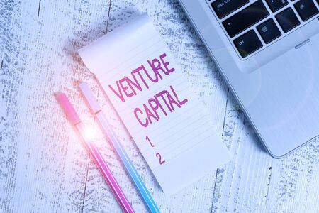 Text sign showing Venture Capital. Business photo text capital invested in a project in which there is risk Trendy laptop blank ruled notepad pens lying wooden rustic vintage table
