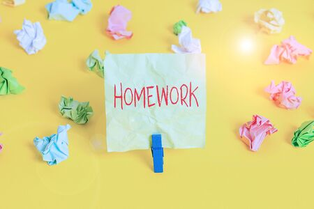 Writing note showing Homework. Business concept for schoolwork assigned to be done outside the classroom or at home Colored crumpled paper empty reminder white floor clothespin Foto de archivo
