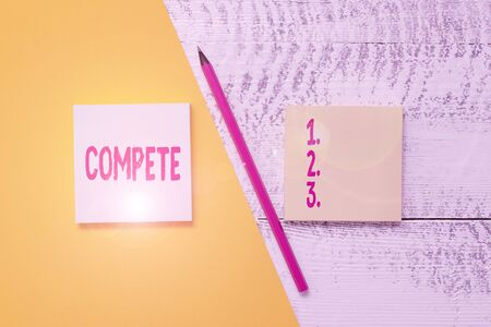Conceptual hand writing showing Compete. Concept meaning win something by defeating or establishing superiority over others Blank notepads pen colored paper sheet wooden background