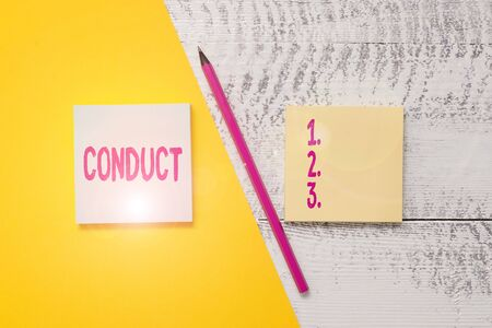 Conceptual hand writing showing Conduct. Concept meaning manner in which an organization or activity is managed or directed Blank notepads pen colored paper sheet wooden background Banque d'images