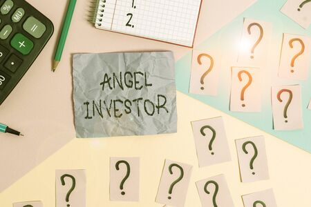 Text sign showing Angel Investor. Business photo showcasing high net worth individual who provides financial backing Mathematics stuff and writing equipment above pastel colours background