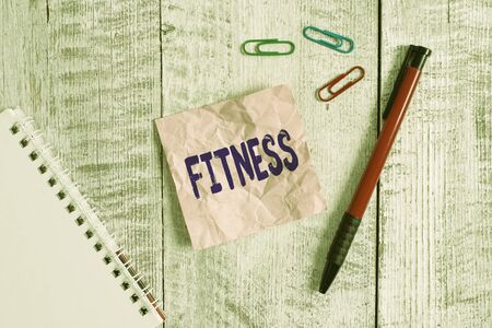 Word writing text Fitness. Business photo showcasing the state of health and wellbeing and the ability to perform Wrinkle paper and notebook plus stationary placed above wooden background