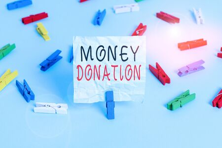 Conceptual hand writing showing Money Donation. Concept meaning something which someone gives to a charity or other Colored clothespin papers empty reminder blue floor officepin