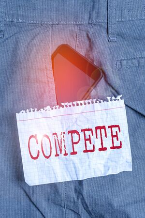 Word writing text Compete. Business photo showcasing win something by defeating or establishing superiority over others Smartphone device inside formal work trousers front pocket near note paper Banque d'images