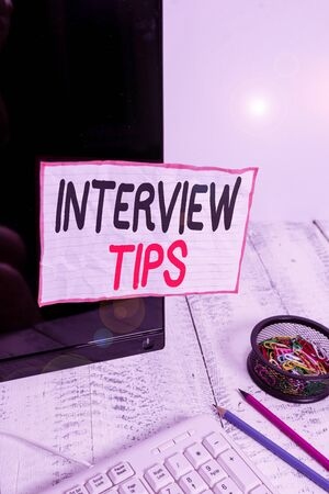 Handwriting text writing Interview Tips. Conceptual photo information or advice given to be helpful during interview Note paper taped to black computer screen near keyboard and stationary