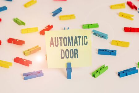 Word writing text Automatic Door. Business photo showcasing opens automatically when sensing the approach of person Colored clothespin papers empty reminder white floor background office Stockfoto