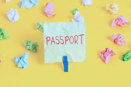 Writing note showing Passport. Business concept for official document issued by a government certifying the identity Colored crumpled paper empty reminder white floor clothespin