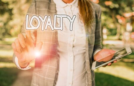Conceptual hand writing showing Loyalty. Concept meaning faithfulness to commitments or obligations Quality of staying firm Business woman sitting with mobile phone and cup of coffee Stock Photo