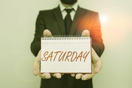 Word writing text Saturday. Business photo showcasing First day of the weekend Relaxing time Vacation Leisure moment Male human wear formal work suit office look hold mathematics book use hand