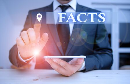 Handwriting text Facts. Conceptual photo information used as evidence or part of report news article blog Male human wear formal clothes present presentation use hi tech smartphone