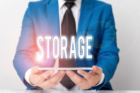 Word writing text Storage. Business photo showcasing Action of storage something for future use Keep things safe Businessman in blue suite with a tie holds lap top in hands Zdjęcie Seryjne