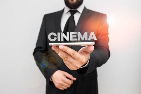 Handwriting text writing Cinema. Conceptual photo theater where movies are shown for public entertainment Movie theater Male human wear formal work suit hold smart hi tech smartphone use one hand Banco de Imagens