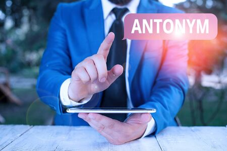 Writing note showing Antonym. Business concept for word or phrase whose meaning is the opposite of another word Businessman with pointing finger in front of him Reklamní fotografie