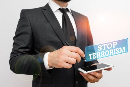 Text sign showing Stop Terrorism. Business photo text Resolving the outstanding issues related to violence Male human wear formal work suit hold smart hi tech smartphone use one hand