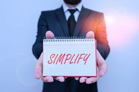 Word writing text Simplify. Business photo showcasing make something simpler or easier to do or understand unravel Male human wear formal work suit office look hold mathematics book use hand