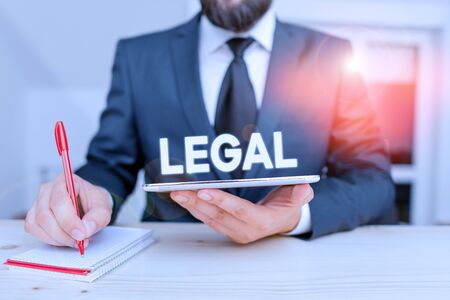 Word writing text Legal. Business photo showcasing Allowable or enforceable by being in conformity with the law Male human wear formal clothes present presentation use hi tech smartphone