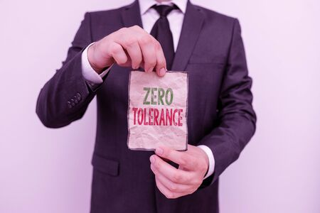 Handwriting text Zero Tolerance. Conceptual photo refusal to accept antisocial behaviour or improper behaviour Male human wear formal work suit office look hold notepaper sheet use hand