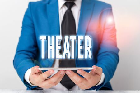 Word writing text Theater. Business photo showcasing building or outdoor area in which plays and dramatic perforanalysisces Businessman in blue suite with a tie holds lap top in hands