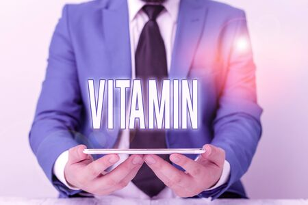 Word writing text Vitamin. Business photo showcasing group of organic compounds which are essential for normal growth Businessman in blue suite with a tie holds lap top in hands