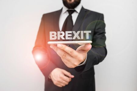 Handwriting text writing Brexit. Conceptual photo term potential departure of United Kingdom from European Union Male human wear formal work suit hold smart hi tech smartphone use one hand