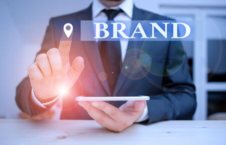 Handwriting text Brand. Conceptual photo Type of product manufactured by a company under a particular name Male human wear formal clothes present presentation use hi tech smartphone