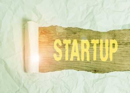 Writing note showing Startup. Business concept for the action of setting something in motion newly established business Cardboard which is torn placed above a wooden classic table
