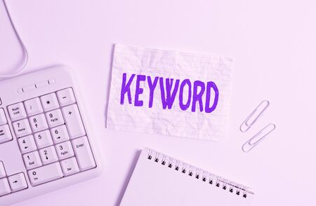 Handwriting text Keyword. Conceptual photo word which acts as the key to a code Concept of great significance White pc keyboard with empty note paper above white background