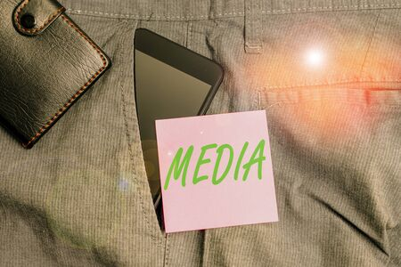 Handwriting text Media. Conceptual photo the main means of mass communicationthat are regarded collectively Smartphone device inside trousers front pocket with wallet and note paper Banque d'images