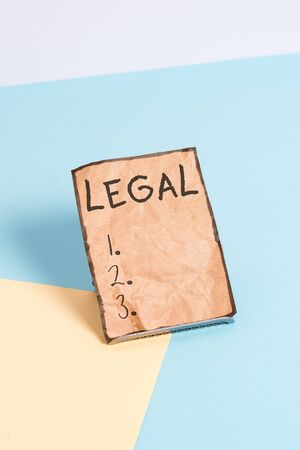 Writing note showing Legal. Business concept for Allowable or enforceable by being in conformity with the law Paper on buffer wire on soft pastel multi colours backdrop