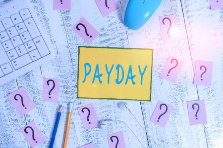 Text sign showing Payday. Business photo showcasing a day on which someone is paid or expects to be paid their wages Writing tools, computer stuff and scribbled paper on top of wooden table