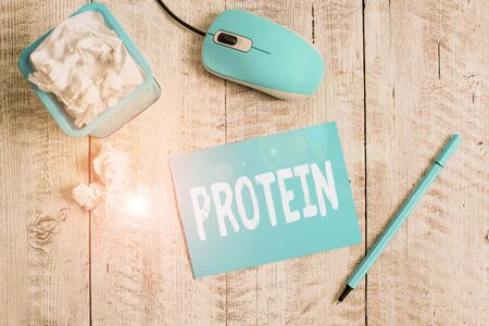 Text sign showing Protein. Business photo showcasing the low in fat or carbohydrate consumption weight loss plan Crumpled paper in bin and computer mouse with stationary on wooden backdrop