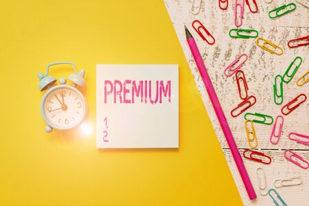 Word writing text Premium. Business photo showcasing something or someone of greater or superior quality A reward Notepad marker pen colored paper sheet clips alarm clock wooden background