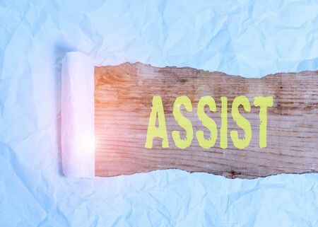 Writing note showing Assist. Business concept for help them to do a job or task by doing part of the work for them Cardboard which is torn placed above a wooden classic table Imagens
