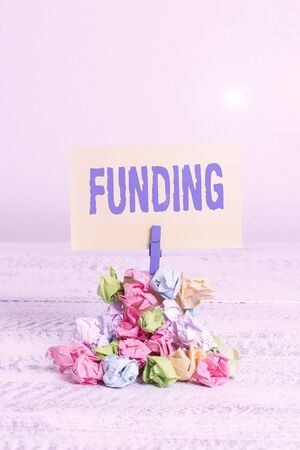 Handwriting text writing Funding. Conceptual photo money provided by an organization or government for a purpose Reminder pile colored crumpled paper clothespin reminder white wooden space