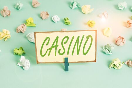 Writing note showing Casino. Business concept for a building where games especially roulette and card games are played Colored crumpled papers empty reminder blue floor background clothespin