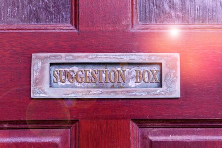 Handwriting text writing Suggestion Box. Conceptual photo container which showing can leave comments about something Old retro mailbox on the wooden doors. Hole on the wooden doors for mail