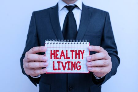 Text sign showing Healthy Living. Business photo showcasing way of living that lowers the risk of being seriously ill Male human wear formal work suit office look hold mathematics book use hand