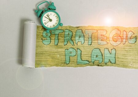 Text sign showing Strategic Plan. Business photo showcasing analysisagement activity that is used to set and focus priorities Alarm clock and torn cardboard placed above a wooden classic table backdrop Banco de Imagens
