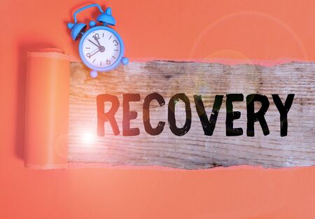 Handwriting text writing Recovery. Conceptual photo the return to normal state of health mind or strength soon Alarm clock and torn cardboard placed above a wooden classic table backdrop