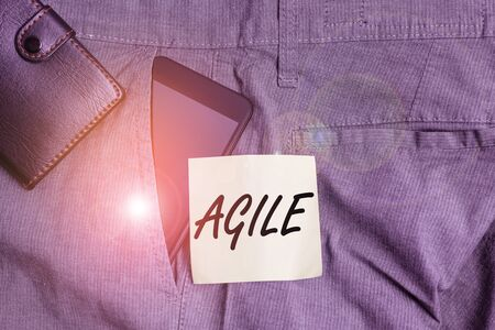 Word writing text Agile. Business photo showcasing particular approach to project management that is utilized in software Smartphone device inside trousers front pocket with wallet and note paper 写真素材