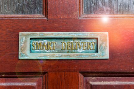 Handwriting text writing Smart Delivery. Conceptual photo Mobile solution for delivering and transporting goods faster Old retro mailbox on the wooden doors. Hole on the wooden doors for mail
