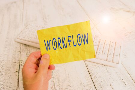 Text sign showing Workflow. Business photo showcasing Series of activities or procedures necessary to complete a task man holding colorful reminder square shaped paper white keyboard wood floor