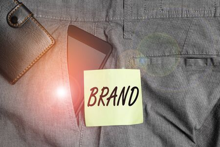 Word writing text Brand. Business photo showcasing Type of product manufactured by a company under a particular name Smartphone device inside trousers front pocket with wallet and note paper 版權商用圖片