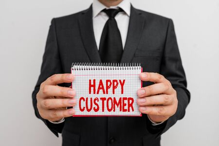 Text sign showing Happy Customer. Business photo showcasing feeling of fulfillment that customers derive from from a firm Male human wear formal work suit office look hold mathematics book use hand Stock Photo