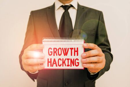 Text sign showing Growth Hacking. Business photo showcasing activity of trying different methods to make a company larger Male human wear formal work suit office look hold mathematics book use hand Stock fotó