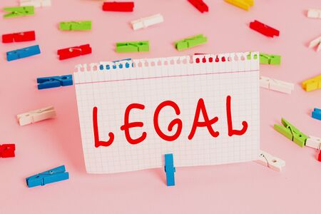 Handwriting text Legal. Conceptual photo Allowable or enforceable by being in conformity with the law Colored clothespin papers empty reminder pink floor background office pin