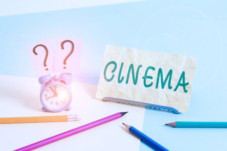 Word writing text Cinema. Business photo showcasing theater where movies are shown for public entertainment Movie theater Mini size alarm clock beside stationary placed tilted on pastel backdrop